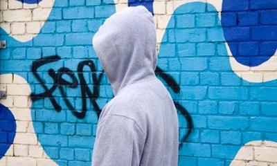 Teenager hanging around dressed in hoodie clothing
